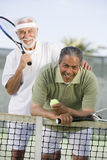 Senior Male Friends Playing Tennis. Portrait of happy senior male friends playing tennis royalty free stock photo