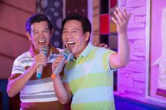 Senior male friends. Singing in karaoke bar Stock Image