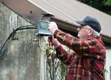 Senior male glasses working outside doing repairs Royalty Free Stock Photos
