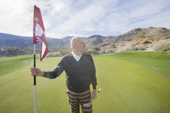 Senior male golfer looking away while holding flag and putter at golf course Stock Image