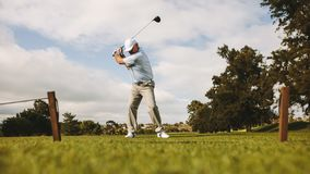 Senior male golfer taking shot stock images