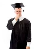 Senior male graduate with hand over his mouth Stock Photo