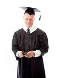 Senior male graduate text messaging on a mobile phone. Senior man in his 60's shot in studio isolated on a white background Royalty Free Stock Photography