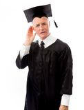 Senior male graduate trying to listen isolated on white backgrou Royalty Free Stock Images