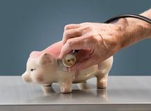 Senior male hand holding stethoscope on piggy bank Stock Images