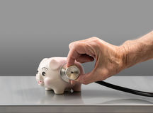 Senior male hand holding stethoscope on piggy bank Royalty Free Stock Images