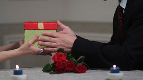 Senior male hands giving gift box to woman stock video