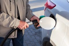 Senior male hands inserting fuel nozzle in a car for gasoline fueling Stock Images