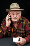 Senior male with hat on phone with white card. Photo senior male with hat on phone with white card Stock Photography