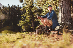 Senior male hiker in forest with a compass Royalty Free Stock Photography