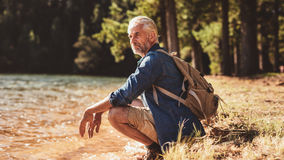 Senior male hiker relaxing by a lake and admiring the view Royalty Free Stock Photos