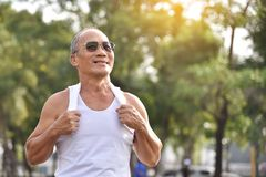 Senior male looking to the sky. Portrait of Asian Senior male wear sunglasses looking to the sky and smiling while exercising at park outdoor background Royalty Free Stock Photos