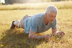 Senior male makes push ups or plank on green grass, has workout outdoor, has flexible body in old age, likes sports exercises, enj. Oys calm atmosphere and Royalty Free Stock Images