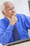 Senior Male Man Businessman Using Computer. A senior man male businessman sitting at a desk wearing a shirt and tue using a computer royalty free stock image
