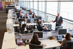 Senior male manager addressing workers in open plan office Royalty Free Stock Photos