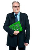 Senior male manager holding big green calculator. Successful senior male manager with a big green calculator in his hand Royalty Free Stock Image