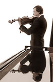Senior male musician plays alto. Senior male musician playing alto, or viola, is reflected in shiny top of the grand piano Stock Photos