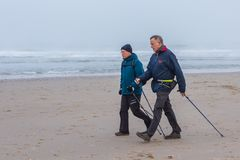 Senior male nordic walkers exercising on the beach. Kijkduin beach, The Hague, the Netherlands - 2 December 2017: senior male nordic walkers exercising on the Stock Image