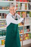 Senior Male Owner Standing Against Shelves In Royalty Free Stock Images