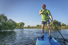 Senior male paddler on paddleboard Royalty Free Stock Image