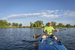 Senior male paddler on paddleboard royalty free stock photos