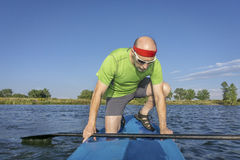 Senior male paddler on paddleboard. Muscular, senior male paddler on a stand up paddleboard on a lake in Colorado Stock Photography