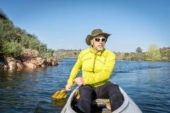 Senior male paddling canoe Stock Photos