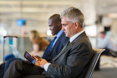 Senior male passenger. At airport using tablet computer while waiting for his flight Royalty Free Stock Image