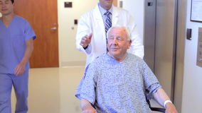 Senior Male Patient Being Pushed In Wheelchair By Doctor stock video footage