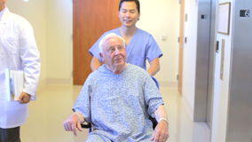 Senior Male Patient Being Pushed In Wheelchair By Nurse stock footage