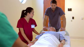 Senior Male Patient Being Wheeled Along Hospital Corridor stock video footage