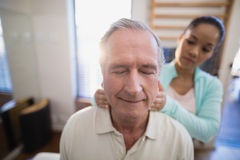 Senior male patient with eyes closed receiving neck massage from female therapist. At hospital ward Royalty Free Stock Image