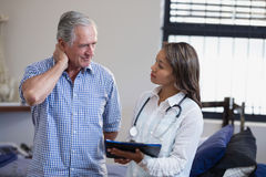 Senior male patient and female therapist discussing file against window Stock Image