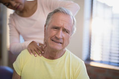 Senior male patient frowning while receiving neck massage from therapist. At hospital ward royalty free stock photography