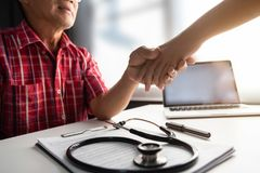 Senior male patient handshaking with Doctor female. royalty free stock image