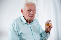 Senior male patient holding urin sample. At the doctor's office royalty free stock photos