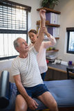 Senior male patient looking up while female doctor examining shoulder. At hospital ward Stock Images