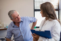 Senior male patient showing back ache to female doctor with file Stock Photography