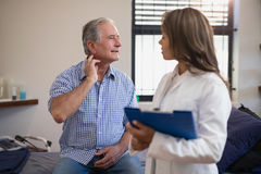 Senior male patient showing neck sprain to female doctor with file Royalty Free Stock Image