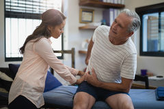 Senior male patient sitting on bed while female therapist examining back stock photo