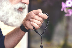 Senior male person calming down himself by counting rosary Royalty Free Stock Photo