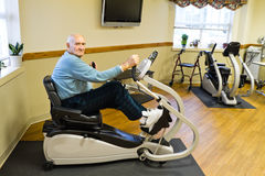 Senior Male Physical Therapy Patient Exercising. Elderly male physical therapy patient sitting and exercising on a recumbent stepper in a rehab gym
