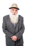 Senior male posing with hat. An old man posing casually to camera over white Stock Photo