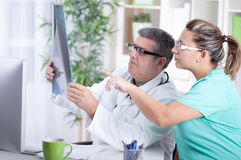 Senior male radiologist and female patient looking at x-ray Stock Photo