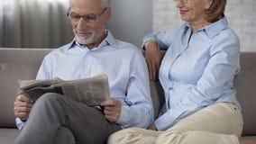 Senior male reading morning newspaper, lady hugging husband tenderly, love. Stock photo royalty free stock photos