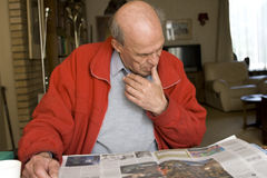 Senior male reading newspaper in his home Stock Images