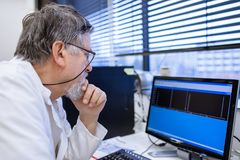 Senior male researcher carrying out scientific research in a lab. Shallow DOF; color toned image Royalty Free Stock Photography