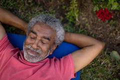 Senior male resting with closed eyes on exercise mat. High angle view of senior male resting with closed eyes on exercise mat at park Royalty Free Stock Photography