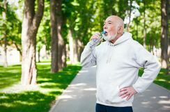 Senior man is having break, drinking water. Senior male runner is having break, drinking water while jogging in park Royalty Free Stock Photography