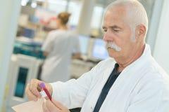 Senior male scientist examining blood test tubes at laboratory. Senior male scientist examining blood test tubes at his laboratory Royalty Free Stock Images